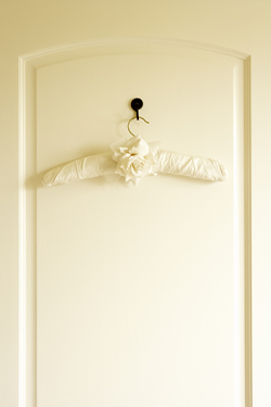 Photo of a white wardrobe door with a padded clothes hanger decorated with a rose