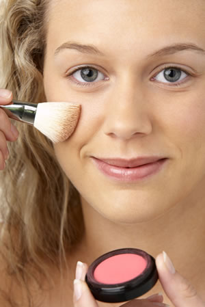 Young woman putting on blush with natural makeup